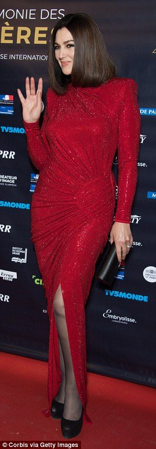 Leggy: She paired the glamorous gown with sheer black tights and tied the look together wi...