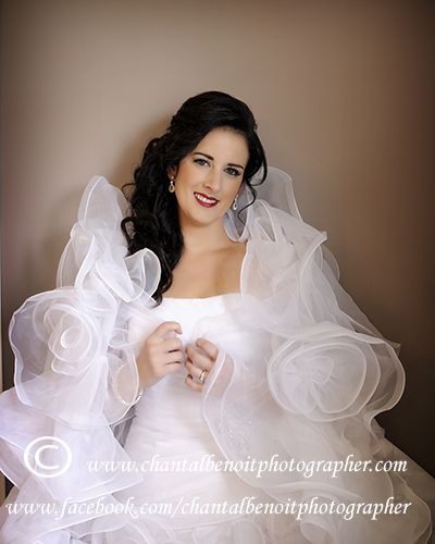 Elegant wedding photo of the bride in her bedroom wrapped in her wedding dress
