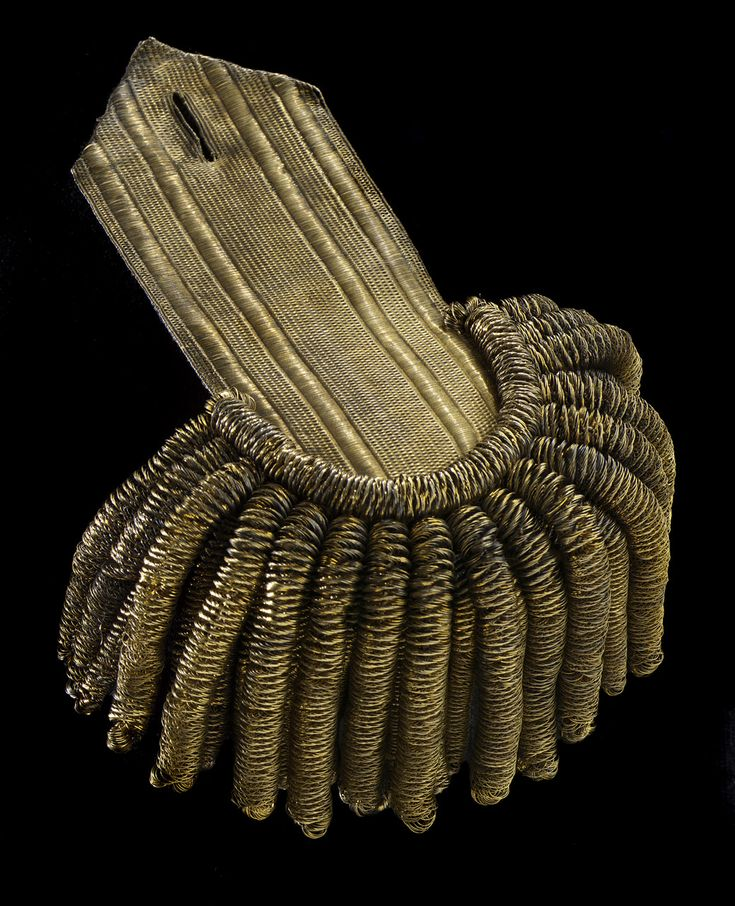 This is an example of a commander's epaulette. The strap is of card covered on one side with wide gold lace in the vellum and check pattern. The reverse is covered with blue silk. The epaulette has two rows of hanging bullions - the outer row features 17 large bullions and the inner row features 17 small bullions. Royal Naval Uniform regulations 1795-1812