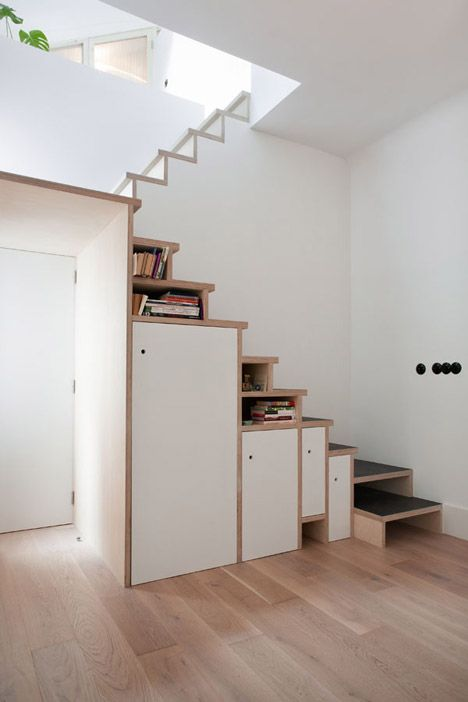A plywood staircase with built-in cupboards and bookshelves frames a doorway in this Madrid apartment
