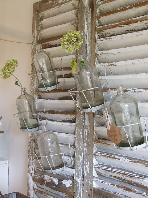 salvaged shutters mounted on wall to display pictures, lanterns, hanging votives, flower pots...
