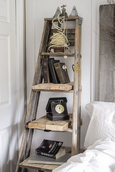 old wooden step ladder closed but leaned against a rustic bedroom wall, with different size boards sticking out from the wall across the rungs, used as shelves for a variety of objects