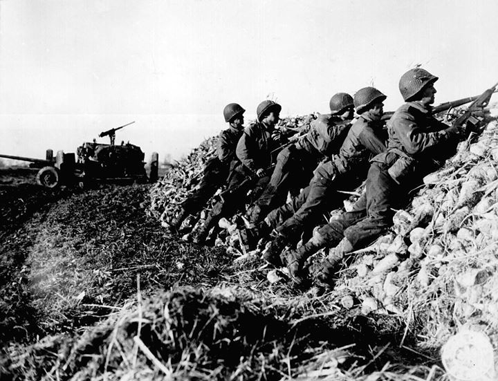 US Army anti-tank infantry searching for the position of a German machine gun that had fired on their vehicle the Netherlands 4 November 1944.