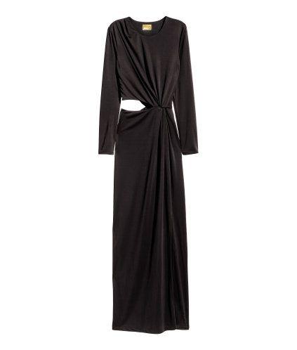 Svart. En lång klänning i stadig trikå med drapering fram. Klänningen har lång ärm och dold dragkedja i sidan. Avskuren i midjan med utskuret parti på ena