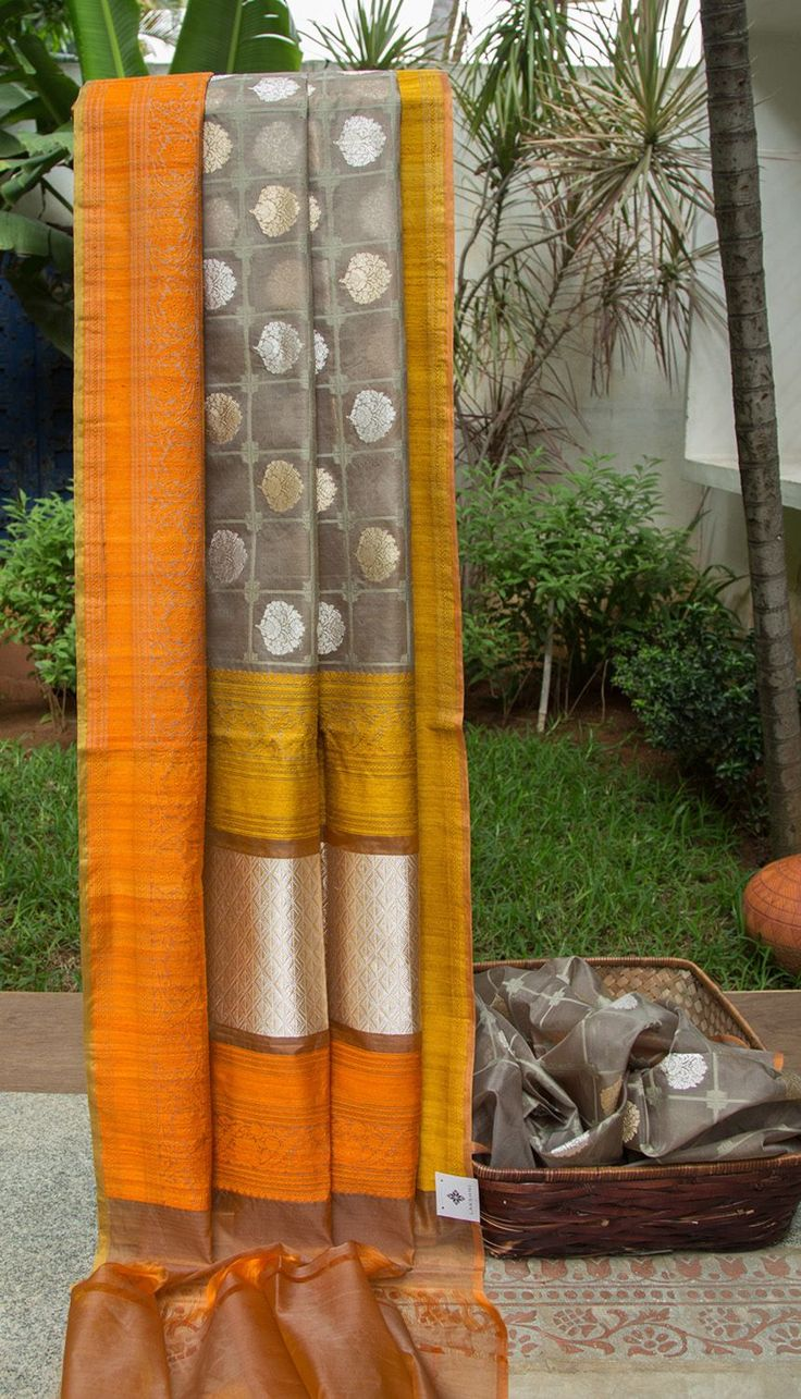 This pebble grey colored kora sari is handwoven in benares and has florals bhuttas woven finely in alternate gold and silver zari, along with similar grey toned thread work. The complementing borde…