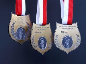 Medale dla absolwentów gimnazjum z wizerunkiem patrona szkoły.Medale wykonane ze złotego laminatu z wklejką z bezbarwnej pleksi.