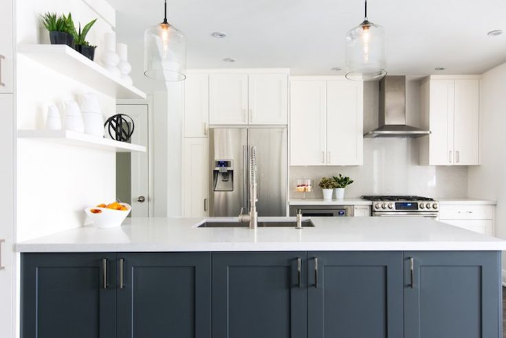 White kitchen with navy blue island. A pair of clear glass light pendants hang over a navy kitchen ...