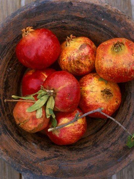 A wooden bowl heaped with pomegranates announce autumn is here in a beautiful way!!