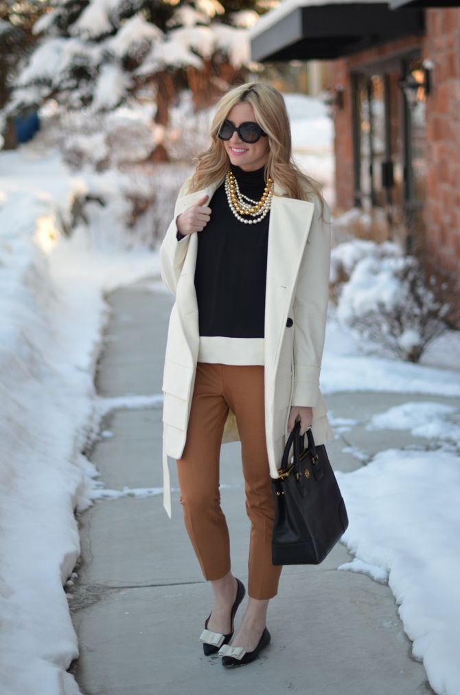 great outfit - black and white sweater, chunky necklace, brown pants, and loafers, with a huge white coat! Classic