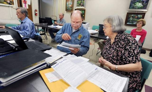 AARP tax assistance volunteer Ed Ard (center) of Madison works with Ruth Chipley (right) of Jackson on filing Monday at the Ridgeland Library. Tax filing deadline is midnight. / Barbara Gauntt/The Clarion-Ledger