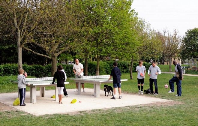 People playing outdoor table tennis Whittington Park Holloway, Islington, London, England, UK