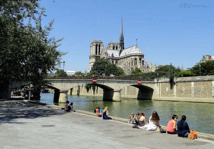 Here you can see the Pont de l'Archeveche which spans across the River Seine and with the famous Notre Dame Cathedral in the background it makes for an impressive view as can be seen with people sitting down enjoying it.  See more www.eutouring.com/images_paris.html