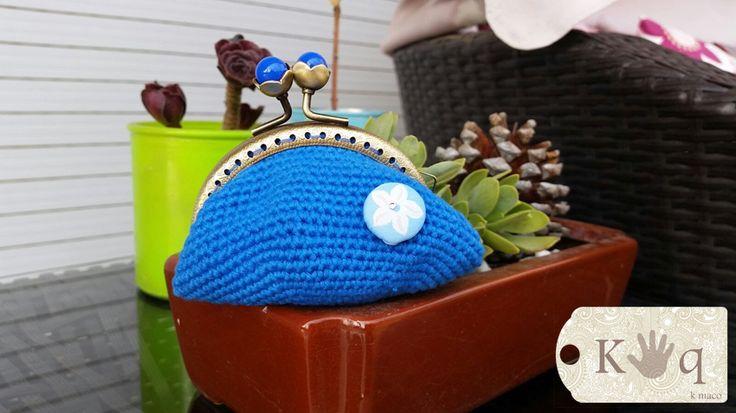 Monedero a crochet de color azul con un botón de decoración