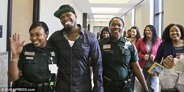 Three Palm Beach County deputies have been disciplined for fawning over 50 Cent while on the job. Pictured: The rapper is flanked by deputies Pamela Gibbs and Yvane Moreland as he leaves Palm Beach County Court last month