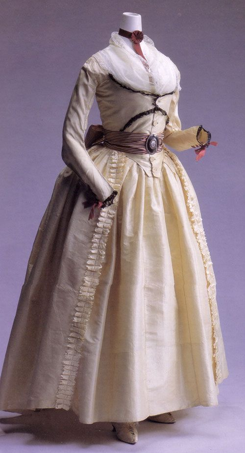 """1790s Robe a L'Anglaise. I call this one the """"Revolution Dress"""" from the Kyoto Fashion Institute. Cream silk taffetta, with a zone/turque-like front and button closure. Black lace decorates the front of the bodice and the cuffs, the latter lacing with wine-colored ribbons. The sash sports a metal buckle with a painted porcelain center, on a striped silk sash."""