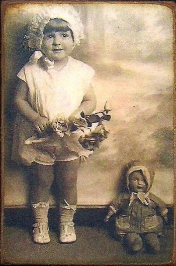 Vintage photo of a little girl with her doll, circa 1920's - 1930's.