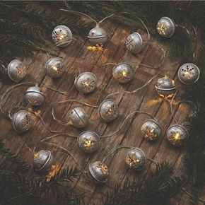 String of Lit Christmas Bells: Silvertone metal bells have quaint star and snowflake cutouts with a single LED in each. Visit Country Door for more Christmas Decorations.