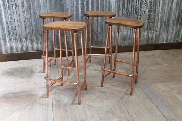 UK-made copper bar stools in two heights. They feature a solid oak seat and copper pipework base, ideal for a bar or bistro. Matching items available.