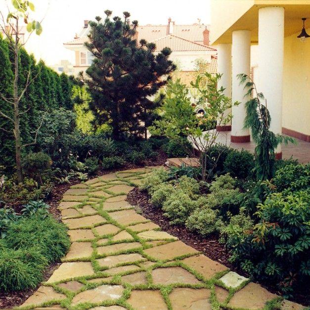 Ścieżka prowadząca z tarasu w głąb ogrodu została wyłożona nawierzchnią kamienną. Jako zielona fuga najlepiej sprawdza się trawa, stosunkowo łatwa w zasadzeniu i pielęgnacji. Fot. Pracownia Sztuki Ogrodowej