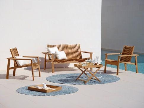 Cane Line: Sitzgruppen aus Holz und witterungsbeständige Outdoorteppiche bringen Wohnlichkeit auf die Terrasse.