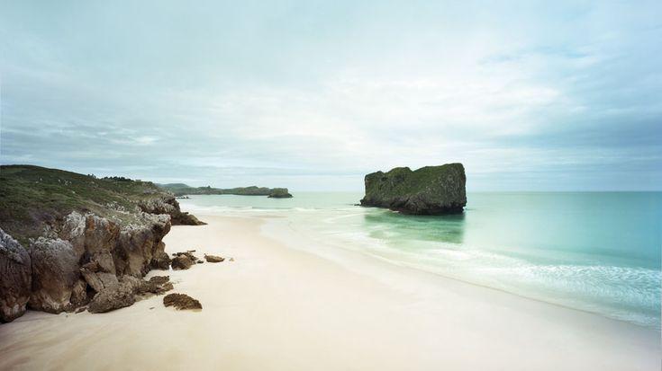 Playa de San Martín, Llanes, un extenso arenal ribeteado de pastizales y cultivos.