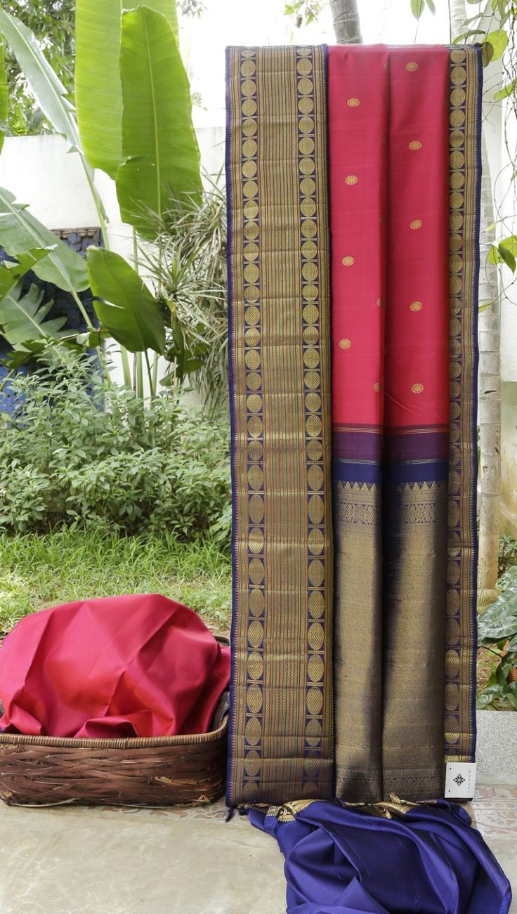 This kanchivaram silk is in dark punch pink with small, round gold zari bhuttas. The border is in navy blue with thread work in basil green and blush red with interesting gold zari work, while the …