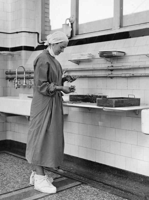 THE NATIONAL HEALTH SERVICE - A nursing sister preparing surgical equipment in an operating theatre of London Hospital.