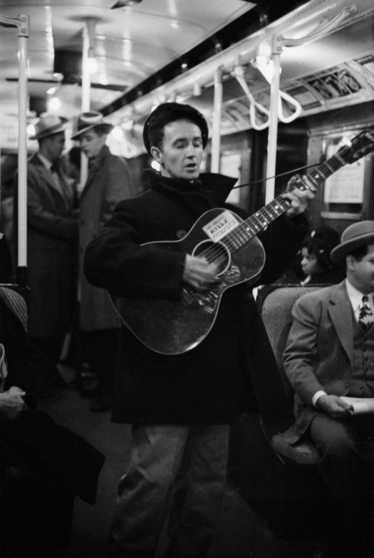 "Woody Guthrie entertains New York commuters in 1943, strumming a guitar he labeled with his now-famous slogan — ""This Machine Kills Fascists.""  Photo: Eric Schaal—Time & Life Pictures/Getty Image"