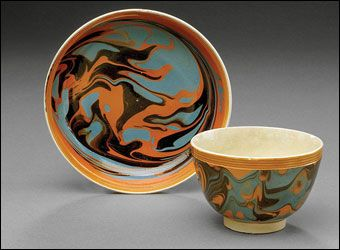 Mochaware - Unusual British creamware mochawear handleless cup and saucer, ca. 1800. Each slip marbled in black and slate blue on a pumpkin field within rouletted orange-glazed reeded borders. Diameter 3 1/2
