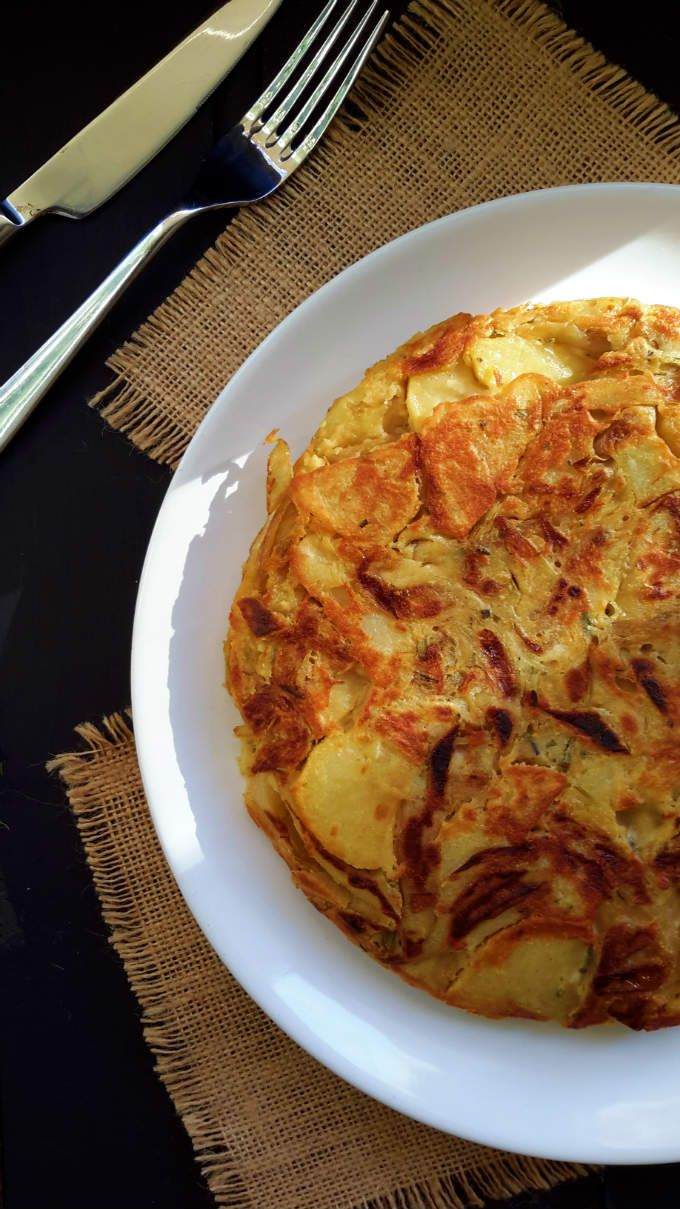 Vegan Spanish omelet with caramelized onions, roasted garlic and rosemary. An easy and delicious take on the traditional tortilla de patatas.