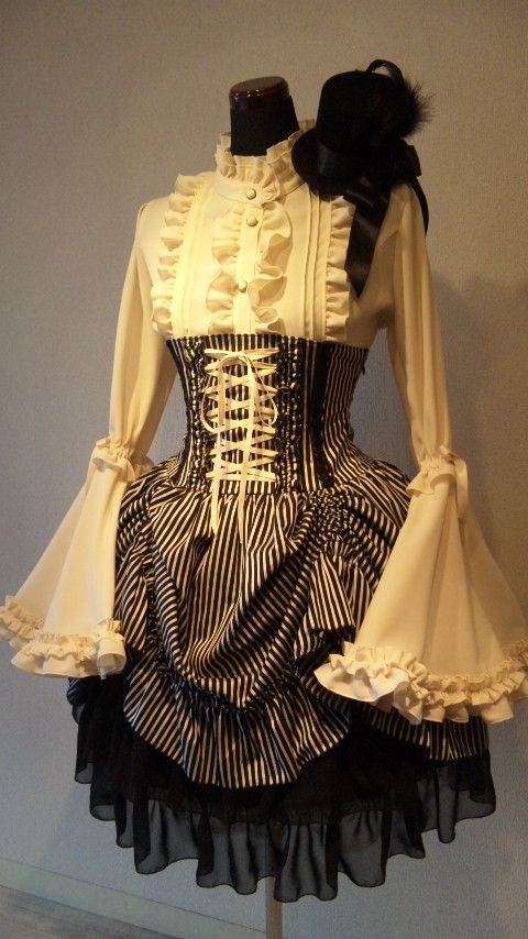 this is gorgeous - lolita goth. Love the high waisted corset skirt over the ruffled shirt. Great use of lace on the edge/under the skirt and on the shirt. Muted colors allow for more wild shapes and textures without looking completely like a costume, though this outfit is probably not everyday wear.