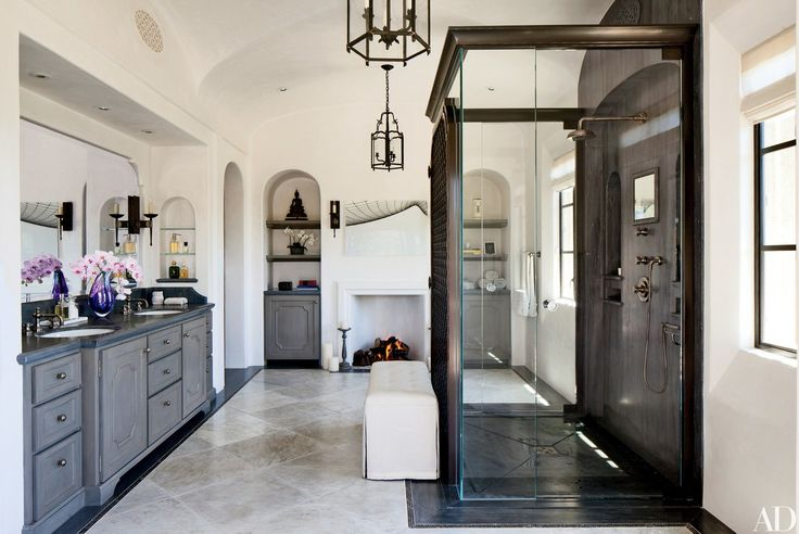 Arched wall niches hold toiletries, towels, and art in the master bath of Gisele Bündchen and Tom Brady's Los Angeles home, which was designed by architect Richard Landry and decorator Joan Behnke. Installed in the space are lanterns by Dennis & Leen, Kallista sinks, and turquin-blue-marble counters from Compas Architectural Stone, which also designed the sink and shower fittings; the artwork above the fireplace is a photograph of Gillette Stadium (where the Patriots play) by Jon Coulthard.