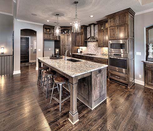 open kitchen with large granite island beautiful lighting