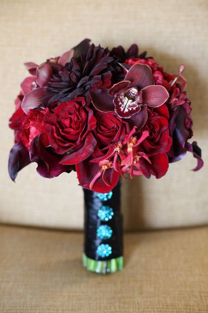 "burgundy roses, dahlias, cymbidium orchids, calla lilies and james storey orchids. I like the contrasting ""buttons"""