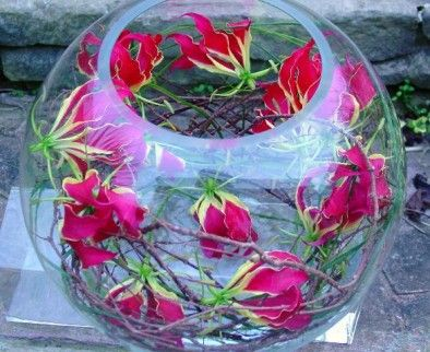 Gloriosa fish bowl    The stunning gloriosa lily, teamed with willow in this large gold fish bowl makes a different and striking table centre.