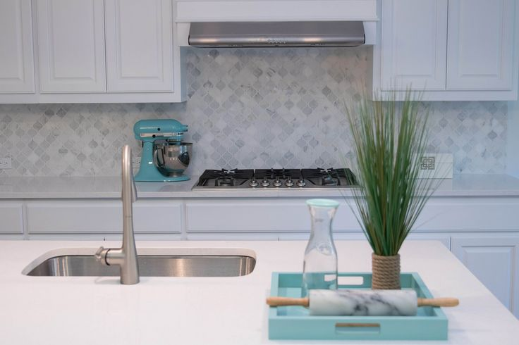 Beautiful white Kitchen equipped with white shaker cabinets, white carrara lantern tile.   Jazzed up with Crate and Barrel's Zuma Aqua Tray and marble rolling pin!