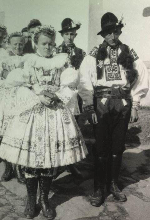 Mládenec s družičkou na svatbě Čechově ze Lhotky 16.10.1951, foto Beneš  Každý mládenec má od družičky darovanou vonicu na klobouku. Jinak má kostelový kroj. Dručica má věneček a k tomu tedy bílý fěrtoch, jak patří k obřadnímu kroji.  Hradcovice 1951