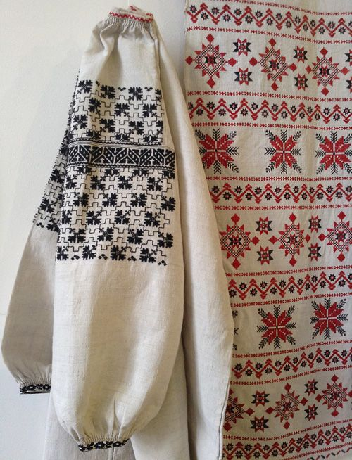 Embroidery designs on the sleeve of a female shirt and on festive towel. The shirt is embroidered with black threads, but it doesn't mean it's a shirt for mourning. Black color is often used in Ukrainian traditional embroidery patterns. The towel is embellished with red and black embroidery