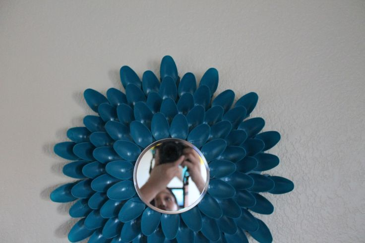 I made this with my roommate! It is just two packages of spoons and a mirror from the dollar tree. I also used cardboard for backing (just from cereal boxes). We used some teal spray paint from Home Depot and viola! cute little flower mirror for our living room :)