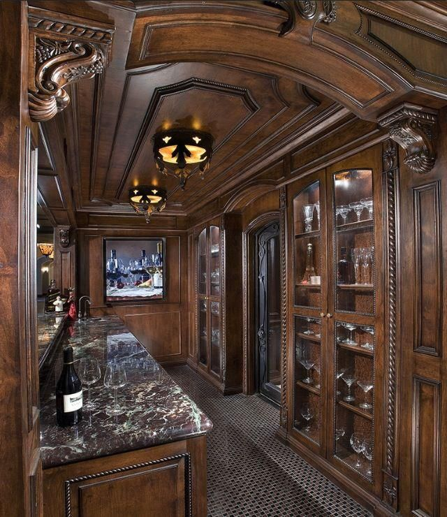 Now THIS is a wine cellar... LOVE the dark woods, architectural detailing... amazing