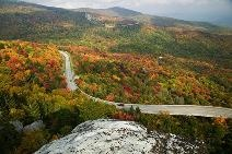 """Blue Ridge Parkway.  Planners saw the road as the first use of the parkway idea.  Stanley W. Abbott was the landscape architect who guided the parkway's design and central themes.  Along the two-lane road, there is not a single billboard, stop sign or traffic light. Utilities are buried. The parkway succeeds in fulfilling Abbott's desire to eliminate the """"parasitic and unsightly border development of the hot-dog stand, the gasoline shack, and the billboard"""" so that the natural scenery…"""