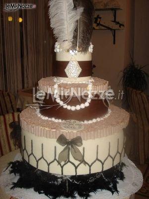 http://www.lemienozze.it/operatori-matrimonio/catering_e_torte_nuziali/torte-nuziali-monza-e-brianza/media/foto/11  Torta nuziale multipiano con piume e perle per richiamare il tema del charleston