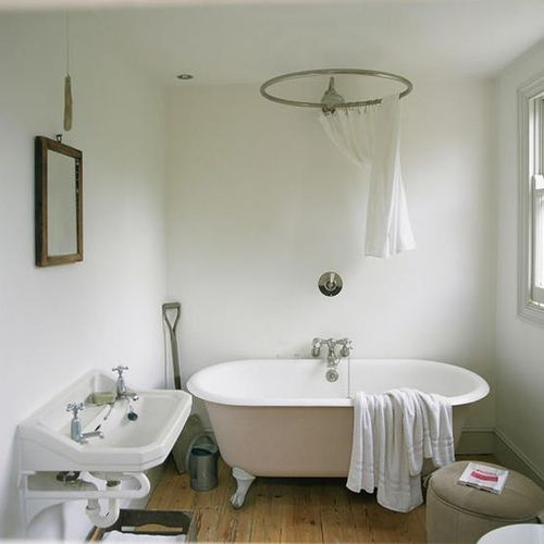 soft pink clawfoot tub with center wallmounted faucet and round shower curtain