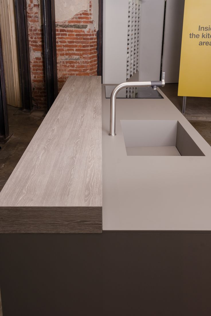 FENIX NTM super matte surfaces with a warm brick wall make a contemporary kitchen in this industrial loft style design.