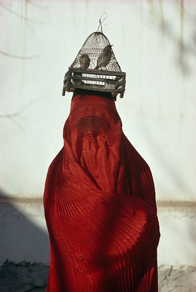 Credit: Thomas J Abercrombie/National Geographic Magazine/Chris Beetles Gallery A woman draped in a red chadri carries goldfinches in a cage on her head in Kabul, 1968