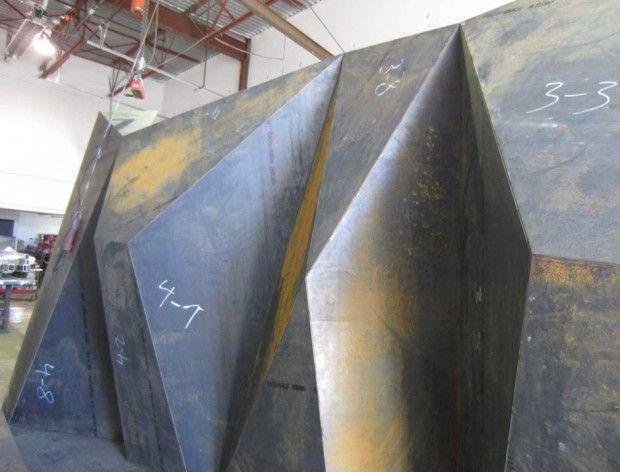 Solution au problème d'érosion. Barrière-sculpture en acier Corten. La forme abstraite de cet ouvrage sert à canaliser l'énergie des vagues et à faciliter le dépôt de sable sur la plage. Vancouver, Canada. Architecte paysagiste: Paul Sangha, http://www.paulsangha.com/.