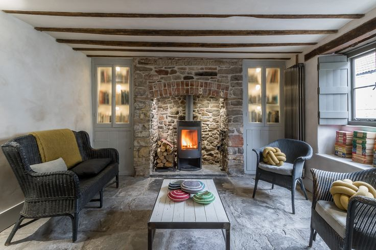 Miner's Cottage II - lounge in a renovated eighteenth century cottage with feature stone fireplace, grey cupboards, log burner, exposed beams, flagstones , shutters, and lime plastered walls