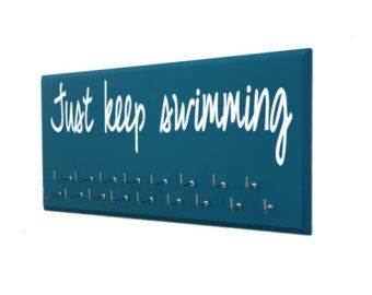 swimmer gifts, swimming, swimmer gift, swim, just keep swimming, swimmer, ribbon, swimming ribbons, ribbon display, swim team, trophy You have earned those medals, you deserve to show them off! As runners, we all know how it feels to run on the wall, through it and past it! Now it's time to reward yourself with a running medals hanger! Or perhaps congratulate the athlete in your life with the perfect gift for runners. All of our medals display racks are designed by runners (us) for runners…