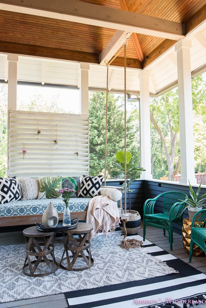 A back porch makeover that oozes comfort and pops of color everywhere. Featuring printed pillows, layered rugs, and hanging flowers.
