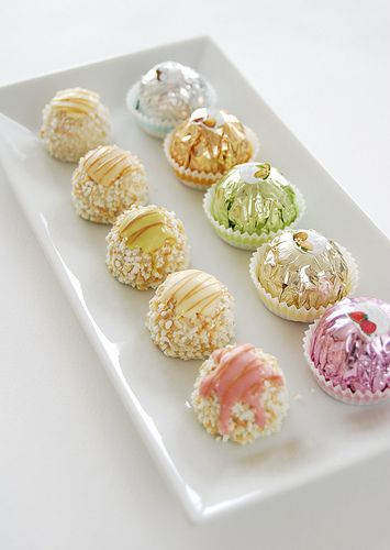 They are Ferrero Chocolates and this is the Ferrero Garden collection, consisting of flavors such as strawberry, pistachio, raspberry, coconut, lemon, almond, and hazelnut.    They are filled with half almonds, creams in corresponding flavors, crisp wafer cookies, and icing caps.    They look like little gifts wrapped in shimmery, foiled, candy colors and nested in delicate, floral-hued, confection liners.